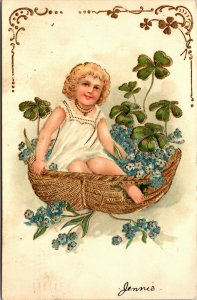 GIRL IN A BASKET WITH FLOWERS CLOVERS  - VINTAGE POSTCARD