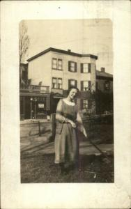 Woman Works Garden - Store & Bldg in Background - Boston MA Cancel RPPC