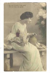 Woman sitting on bench holding Pigeons, Wer den Taubchen Futter giebt, Wird v...
