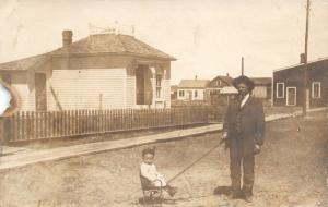 Real Photo Post Card~Man Pulls Baby Boy in Tiny Wheel Chair~Dirt Road~c1910 RPPC