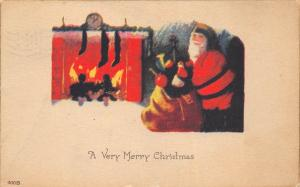 Merry Christmas 1910 Postcard Fireplace with Stockings Santa Claus Bag of Toys