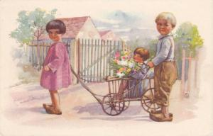 SOUKUP: Girl & Boy in Wooden Clogs Pulling Toddler w/ Flowers in Wooden Wagon...