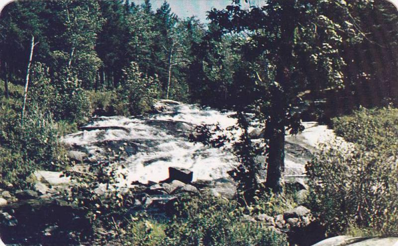 The waters of Rushing River tumble down over the rocks,  provincial roadside ...