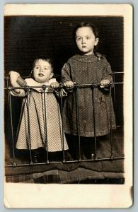 RPPC Toddler w/Bottle and Big Sister Stand Behind Metal Bed Railing~c1910