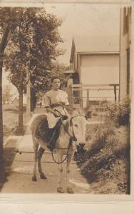 RP; Boy riding Donkey on a sidewalk, 1900-10s
