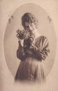 Woman holding cluster of grapes wearing a long satin dress, 00-10s