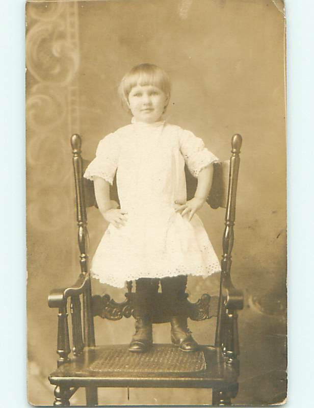 Pre-1918 rppc CUTE GIRL IN BUTTON SHOES STANDS ON ANTIQUE CHAIR r5910