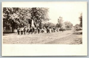 Sepia RPPC Town Sidewalk March~Led by Saxophone~Trombone~Tuba~Trumpet~Flag c1910