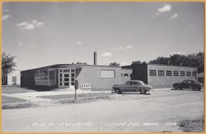RPPC-Sleepy Eye, Minnesota - R.E.A. Building with 1950's autos out front - 1953