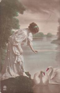 Woman approaching swans in a lake, 00-10s