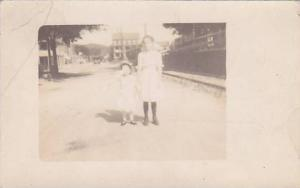 RP; Two girls standing on middle of street, smaller girl covering eyes, PU-1912