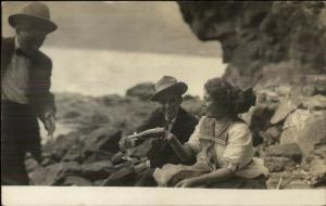 Man & Woman on Rocks Pouring Drink Bottle & Glass c1910 Real Photo Postcard