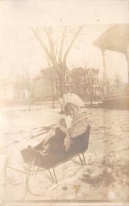 Jacksonville Illinois~Little Girl Bundled Up in Baby Sleigh~Snow~Homes~1912 RPPC
