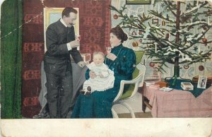 Postcard artist signed painting Christmas scene couple and child