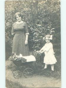 rppc 1912 GIRL PUTS HER DOLL INTO THE BABY CARRIAGE AC8183