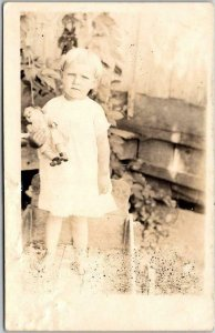 Vintage RPPC Real Photo Postcard Not-So-Happy Girl in Yard w/ Doll - c1910s
