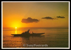 Tahitian fisherman at dusk in the lagoon. - Un pencheur Tahitien a la tombee de