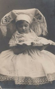 Girl in German traditional white dress & head wear holding pillow, PU-1909