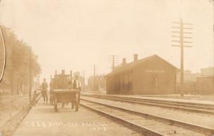 Earlville Illinois~CB&Q Depot~Men Walk Railroad Wagons on Boardwalk~1911 RPPC