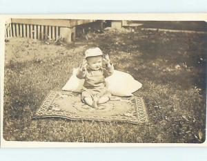 Pre-1918 rppc CHILD IN HAT SITTING ON ANTIQUE CARPET RUG ON GRASS HL9924