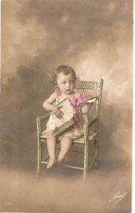 Little girl sitting in chair Old vintage antiue postcard