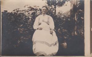 RP: Woman in full length dress posing with hand held fan, 1900-10s