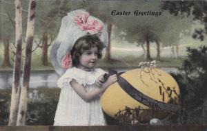 Easter Greetings, Girl wearing bonnet, leaning on large yellow egg with black...