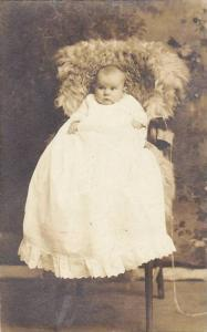 RP; Baby dressed in long white gown, siting in fur-covred high chair, 00-10s