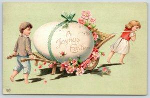 EAS Easter~Girl Pulls~Boy Pushes Giant Egg on Wheelbarrow~Lime Back~Emboss~1909