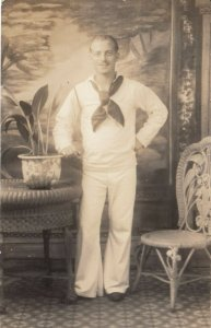 RP: Navy Sailor standing next to potted plant on table, 1918