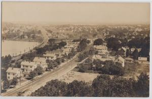 REAL PHOTO view of an unidentified town showing roadway & lots of homes, 1920s