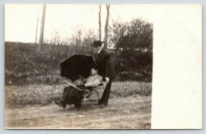 RPPC~Man Pushes His Mother Along A Dirt Road in A Wheelchair~Umbrella~1916 PC