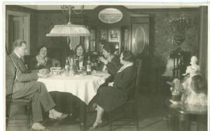 Family sitting around table, 1920s-1930s unused real photo