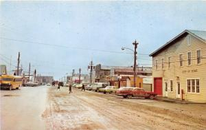 Nome Alsaka~Main Street~City Hall~Storefronts~School Bus~Cars~1960s Postcard