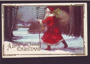 P1558 1923 used postcard santa with bag of gifts approching village