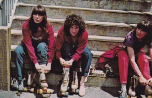 Identical Triplet ladies sitting on staricase steps tieing up roller skates, ...