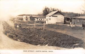 North Dafoe SK~Main Street~TAXI Sign~Dirt Road~Rickety Wood Bldgs~1930s RPPC