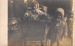 Real Photo Postcard~Girls in Winter Coats~Baby Carriage~Pot Belly Stove~c1908