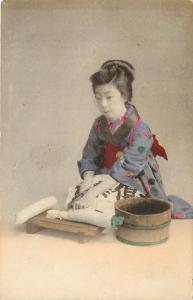 c1910 Hand-colored Postcard; Kneeling Japanese Woman Cuts Daikon Radish w Knife