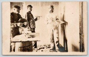 RPPC Caution: Men At Work~Three Men in Coveralls Plaster Wall~Barrel Table~c1910