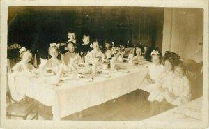 1909 Girls & Boys interior sitting around dinner Table RPPC Postcard 21-10278