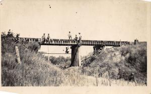 Nebraska~Boys Sitting-Standing on Bridge~One Jumps in Water~c1910 RPPC