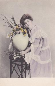 EASTER; Woman holding up a huge white egg on a stool with flowers, 00-10s