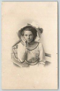 RPPC .Vignette~Vivacious Very Pretty Gal~Hand to Cheek~Leans on Wicker Arm~c1910