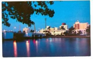 Hotels glow against the evening sky a festival of lights in the dark waters o...