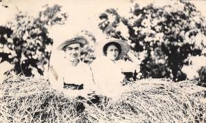 Real Photo Postcard~Couple in Hay Mound~Straw Hats~c1910 RPPC