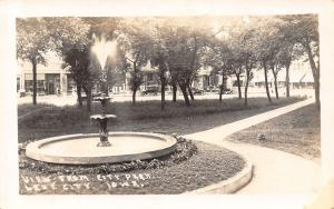 Lake City Iowa~Stores Behind Park Fountain~Ladies Shop~Vintage Cars~c1912 RPPC