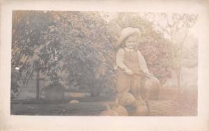 RPPC Little Girl~Bib Overalls Carves A Pumpkin~Log~Wicker Basket~Hand Pump c1910
