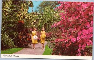 Women in Yellow Dresses walking Azaleas at Sunken Gardens, St Petersburg Florida