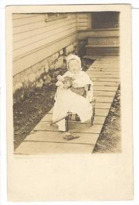 RP: Little girl holds doll sitting in a wagon in front of her house, 10-20s
